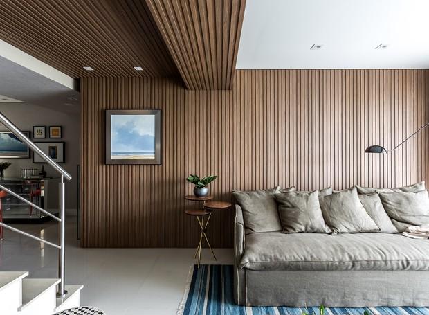 sala-de-estar-painel-ripado-madeira-sofa-tapete-quadro-escada (Foto: Eduardo Macarios/Divulgação)