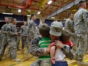 Militar americano reencontra filhos ao voltar do Iraque para os Estados Unidos (Foto: AP)