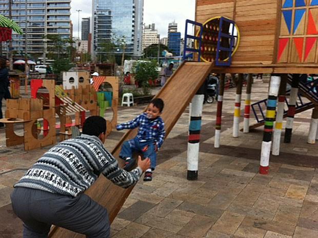 Pai e filho brincam em escorregador montado no Largo da Batata, em São Paulo (Foto: Paula Paiva Paulo)