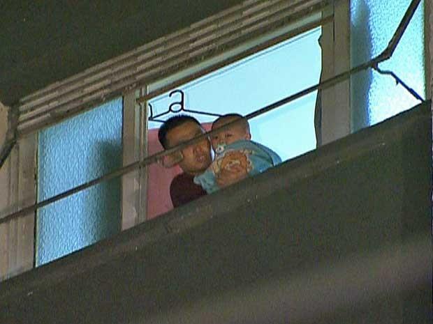 Um homem e um bebê aguardam resgate num apartamento próximo ao prédio que pegou fogo. (Foto: Reprodução / GloboNews)