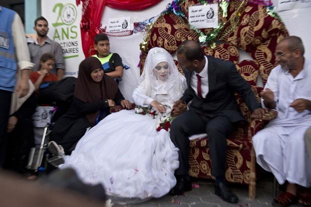 Omar Abu Namar e sua mulher, Heba Fayad, durante seu casamento em uma escola da ONU no campo de refugiados de Shati, na cidade de Gaza, nesta quarta-feira (13) (Foto: Roberto Schmidt/AFP)