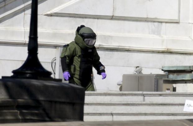 Um policial do esquadrão antibombas inspeciona um pacote suspeito no Capitólio, em Washington, nos EUA, após tiroteio nas imediações (Foto: Jim Bourg/Reuters)