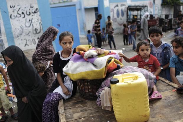 Mulheres e crianças palestinas são vistos nesta terça-feira (29) do lado de fora de escolar da ONU que tem sido utilizada como abrigo para aqueles que deixaram suas casas em meio aos bombardeios de Israel (Foto: Finbarr O'Reilly/Reuters)