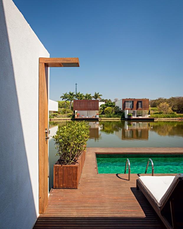 Fundos | Na parte de trás do terreno, o deque foi projetado acima do lago. Do lado esquerdo, gardênias em jardineira executada pela Jardinatto (Foto: Gui Morelli/Divulgação)