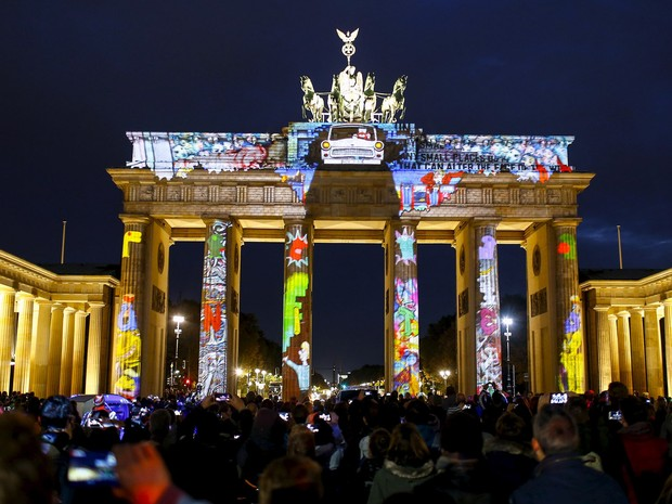 Pessoas observam uma instalação de luz no Portão de Brandemburgo durante a abertura da mostra 'Festival de Luz' em Berlim, na Alemanha. A mostra acontece até o dia 18 de outubro (Foto: Hannibal Hanschke/Reuters)