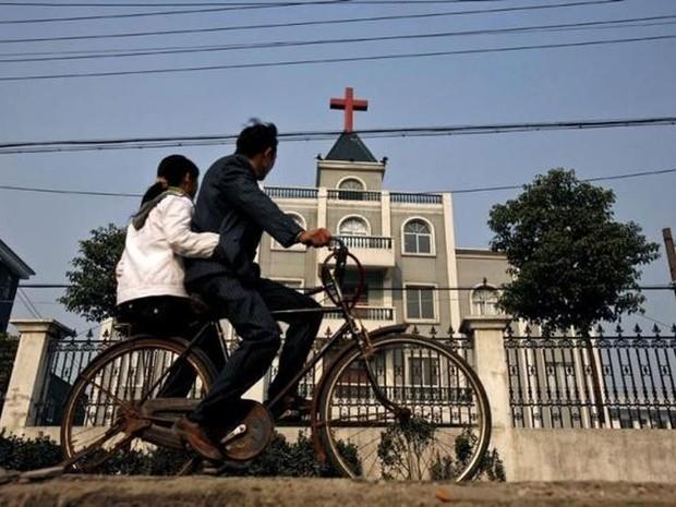 Moradores passam de bicicleta em frente a uma igreja em Xiaoshan, um subúrbio de Hangzhou (Foto: Lang Lang/Reuters)