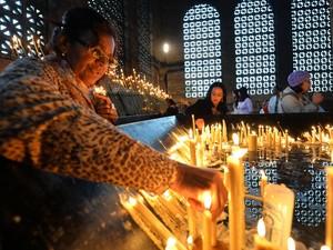 Fiéis acendem velas na Basílica de Nossa Senhora Aparecida (Foto: Nelson Almeida/AFP)