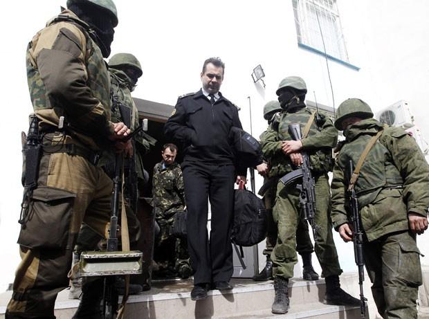 Oficial ucraniano deixa sede da Marinha da Ucrânia em Sebastopol entre homens que acredita-se que estão a serviço da Rússia nesta quarta-feira (19); local foi invadido por milicianos pró-Rússia (Foto: Vasily Fedosenko/Reuters)