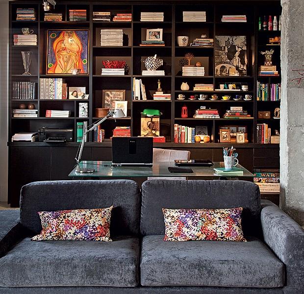 A sala da arquiteta Gabriela Marques conta também com home office. Além da mesa de trabalho, há uma grande estante que mistura elementos dos dois ambientes: livros, fotos de família, xícaras e objetos de decoração. Lá também fica a impressora (Foto: Luis Gomes)