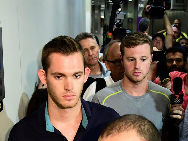 Nadadores Gunnar Bentz (esq.) e Jack Conger deixam delegacia de polícia do Galeão, no Rio, após prestarem depoimento sobre suposto assalto sofrido na cidade (Foto: Tasso Marcelo/AFP)
