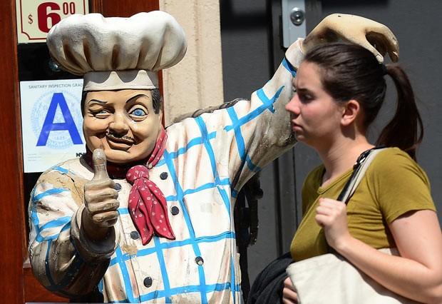Mulher passa por boneco de anúncio de restaurante nesta segunda-feira (8) em Nova York e ganha 'afago' na cabeça (Foto: Emmanuel Dunand/AFP)