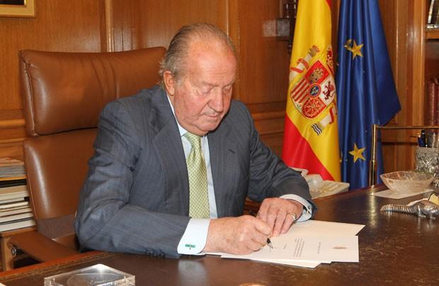 O rei Juan Carlos da Espanha assina sua abdicação no Palácio Zarzuela nesta segunda-feira (2). Ele deixou o cargo após quase 40 anos em favor de seu filho, o príncipe Felipe (Foto: Spanish Royal House/Reuters)