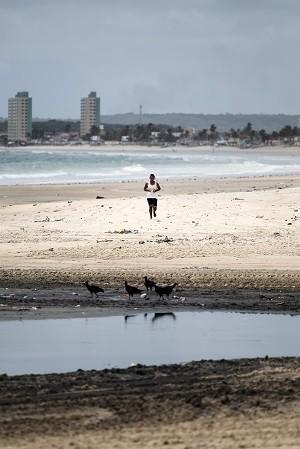 Homem se exercita na praia da Avenida, local onde é despejada a água que percorre pelo Salgadinho (Foto: Jonathan Lins/G1)