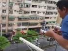 Homem fisga peixe da sacada de prédio em Taiwan