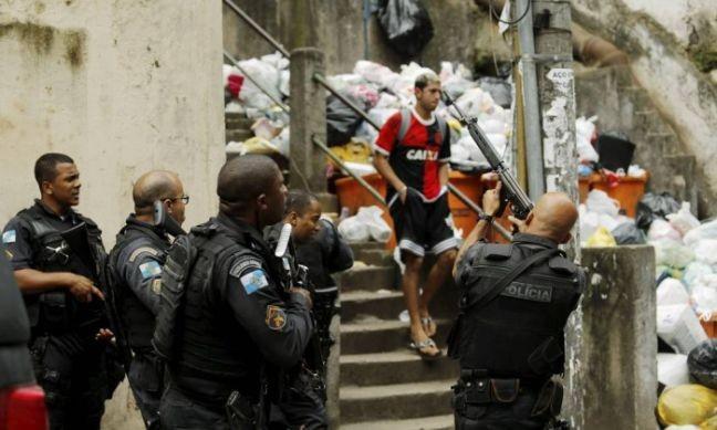 Morador desce as escadas do morro indiferente à ação policial (Foto: Gabriel de Paiva  / Agência O Globo)