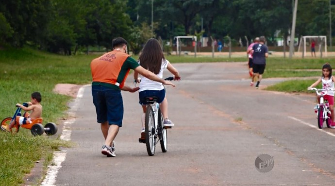 """Voluntário do projeto """"Bike Anjo"""" ajudando as crianças a andarem de bicicleta  (Foto: reprodução EPTV)"""