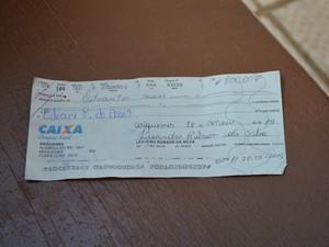 Vítima mostra cheque entregue por casal em loja (Foto: Jeferson Carlos/ G1)