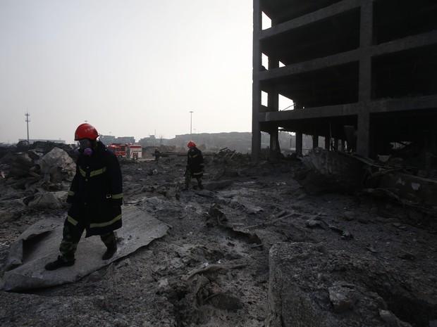 Bombeiros passam por prédio atingido por explosão em Tianjin, na China (Foto: AFP)