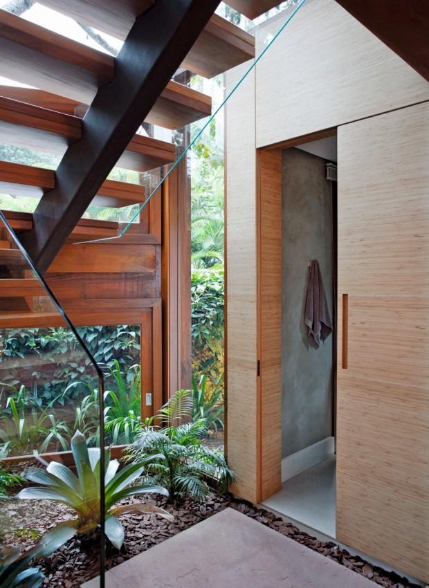 Lavabo Tem painel e porta de lâmina de bambu e, à frente, um jardim de inverno fechado por panos de vidro e cercado pela escada (Foto: Marco Antonio / Editora Globo)