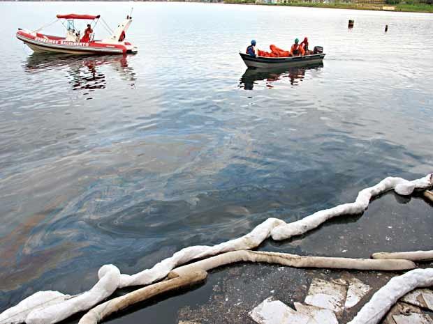Barcos dos bombeiros e da Petrobras navegam pelo Lago Paranoá com mancha de óleo; contenção foi colocada na saída da galeria de águas pluviais (Foto: Lucas Nanini/G1)