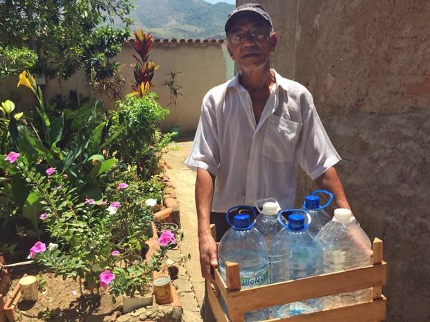 Sebastião Lúcio, morador de Governador Valadares, busca água em poço artesiano duas vezes por semana. Ele não confia na água da rua após lama no Doce (Foto: Cida Alves/G1)