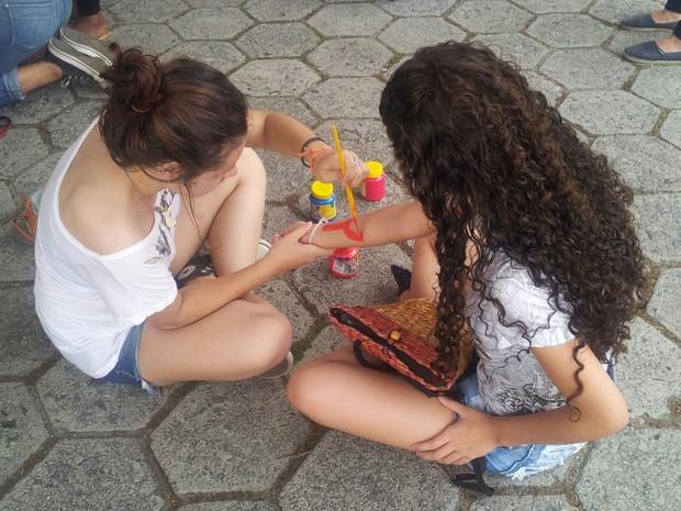 Jovens pintaram o corpo com palavras de ordem e com o simbolo do feminismo (Foto: Naiara Arpini/ G1 ES)