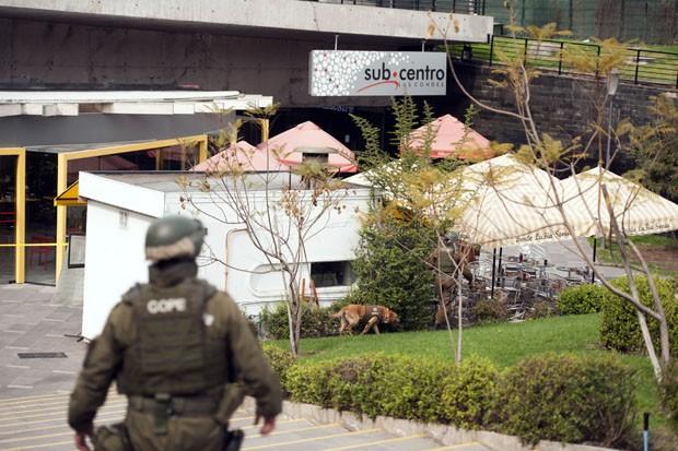 Policial chileno inspeciona a parte externa da estação de metrô Escuela Militar em Santiago, no Chile  (Foto: Vladmir rodas/AFP)