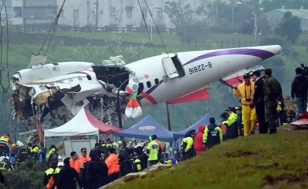 Destroços do avião da Transasia que caiu em Taiwan nesta quarta-feira (4) são retiradas de rio nesta quinta-feira (5) pelas equipes de resgate; 12 pessoas ainda estão desaparecidas (Foto: Sam Yeh/AFP)