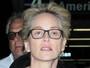 Sem maquiagem, Sharon Stone exibe fios brancos em aeroporto