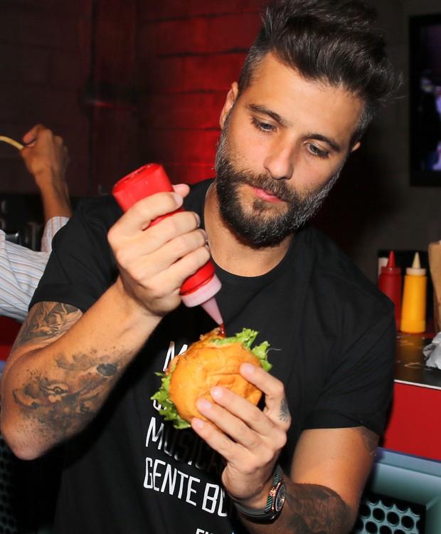 Bruno Gagliasso capricha no molho antes de saborear sanduíche (Foto: Thiago Duran/AgNews)