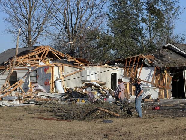 Alan Freeman e Brandon Schmidt observam os estragos provocads por um tornado na casa do irmão de Brandon em Clarksdale, Mississippi, na quinta (24) (Foto: Reuters/Justin A. Shaw)