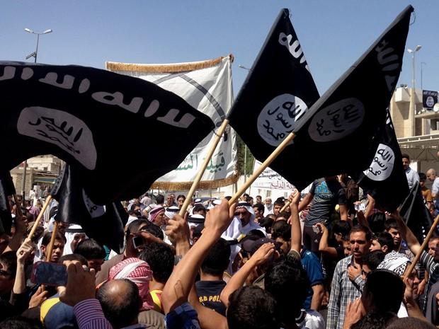 Em foto de 16 de junho de 2014, manifestantes agitam bandeiras do Estado Islâmico em frente à sede do governo de Mossul, no Iraque (Foto: AP Photo/File)