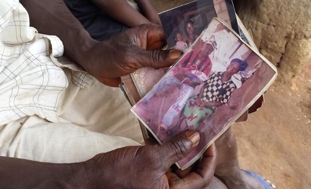 Em foto divulgada pela Unicef nesta quinta-feira (28), uma pessoa segura uma fotografia do menino Emile Ouamouno, ainda bebê: quando tinha 2 anos, o garoto foi a primeira vítima de ebola desta epidemia, e é conhecido como o 'paciente-zero'; ele, sua mãe, (Foto: AP Photo/Unicef/Beukes)