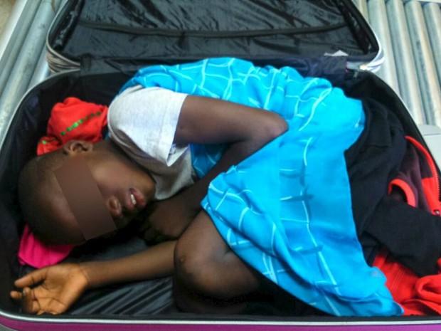 Criança de 8 anos estava espremida em mala quando foi encontrada por autoridades da Espanha (Foto: Ministério do Interior/Reuters)