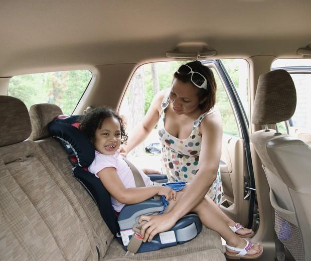 Mãe colocando a filha na cadeirinha (Foto: Thinkstock)