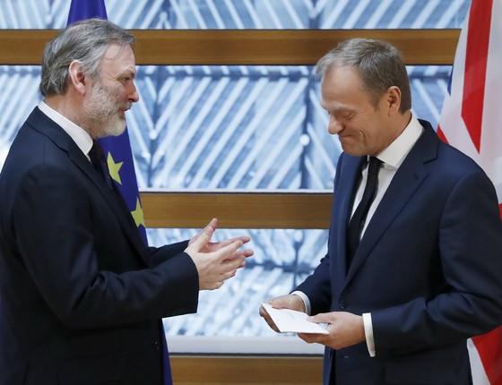 O enviado do Reino Unido Tim Barrow entrega a carta do Brexit para Donald Tusk, presidente do Conselho Europeu (Foto: YVES HERMAN /AFP)