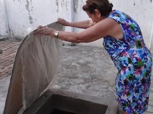 Dona Clauda mostra que tem pouca água no poço (Foto: Michelle Farias/G1)