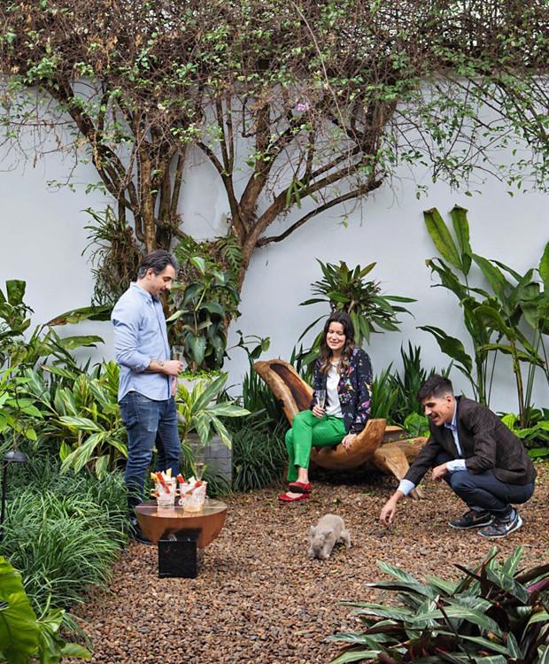 O convidado Conrado Colnaghi (de pé), Vivian e André brincam com o coelho Alfredo no jardim cheio de verde da casa modernista (Foto: Lufe Gomes / Editora Globo)