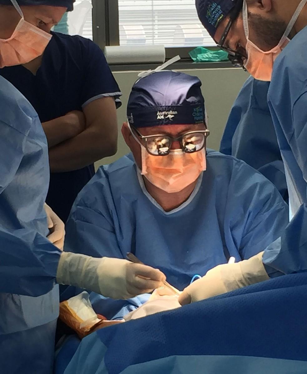 Cirurgião Chris Kimber opera menina Choity Khatun em hostpital de Melbourne  (Foto: HANDOUT / MONASH HEALTH / AFP)