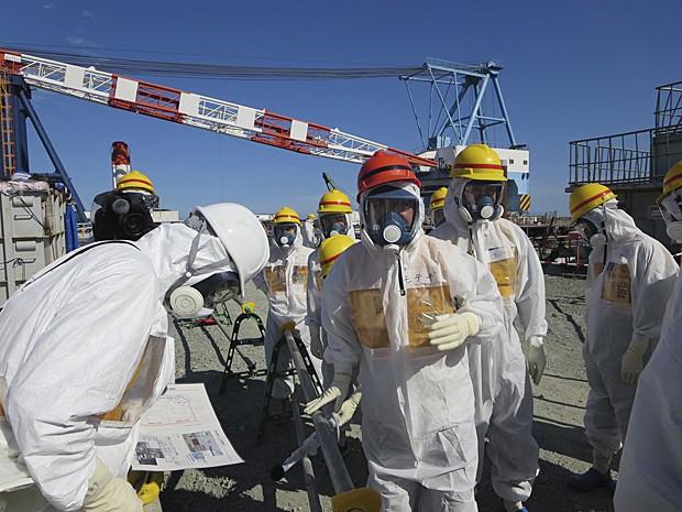 Ministro Toshimitsu Motegi (no centro) usa roupa e máscara de proteção e máscara para inspecionar Tepco nesta segunda (26) (Foto: Tokyo Electric Power Co/Reuters)