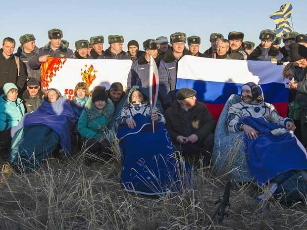 Enrolados em cobertores, a americana Karen Nyberg, o russo Fyodor Yurchikhin e o italiano Luca Parmitano voltaram à Terra com a tocha olímpica de inverno. (Foto: Shamil Zhumatov / Pool / AP Photo)