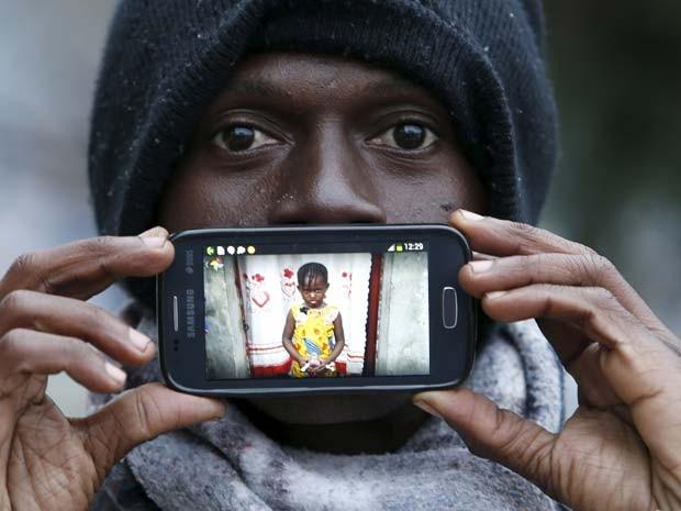Papi, de Kinshasa, no Congo, mostra foto da filha Gisele ao esperar na froteira da Eslovênia com a Áustria (Foto: REUTERS/Srdjan Zivulovic)