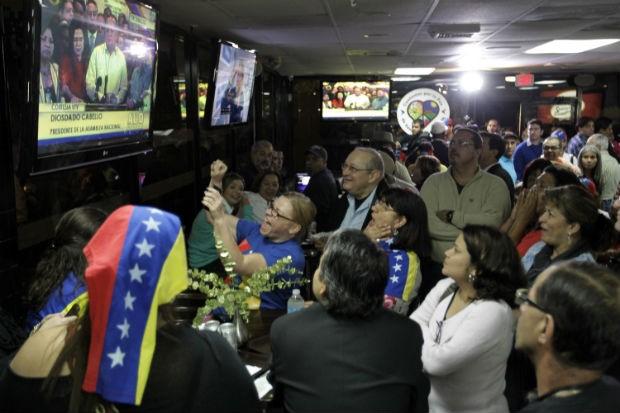 Venezuelanos no restaurante Arepazo 2, em Doral, na Florida, acompanham as notícias sobre a morte de Chávez, na terça-feira (5) (Foto: Luis M. Alvarez/AP)