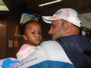 Jennyfer no colo do pai, minutos antes de embarcar, no Aeroporto Afonso Pena (Foto: Aline Lamas/G1)