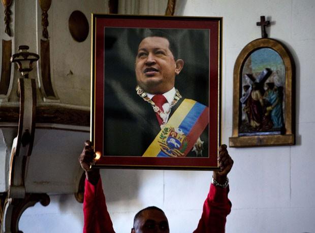Funcionário de embaixada da venezuela segura retrato do presidente em missa dedicada ao líder, em Cuba, nesta terça (8) (Foto: Ramón Espinosa/AP)