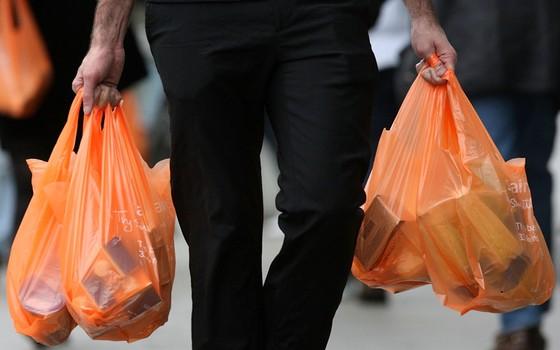 Consumidor carrega compras em sacolas plásticas em Londres, Inglaterra (Foto: Cate Gillon/Getty Images)