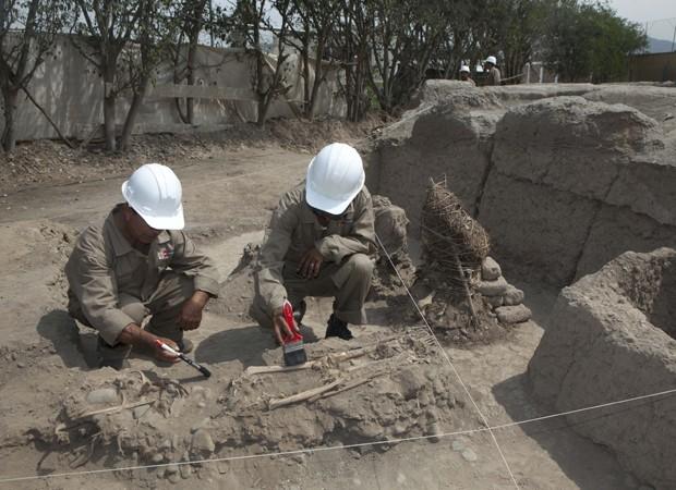 Arqueólogos peruanos limpam ossos de um esqueleto encontrado no complexo esportivo (Foto: Martin Mejia/AP)
