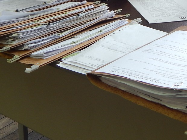Processos judiciais referentes a saúde se acumulam em mesa de secretaria em Divinópolis (Foto: Rodrigo Dias/PMD)