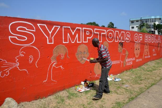 Artista de rua Stephen Doe pinta mural sobre sintomas do ebola em rua de Monróvia, capital da Libéria, onde 1.224 morreram de ebola até esta terça-feira (9) (Foto: AFP Photo/Dominique Faget)