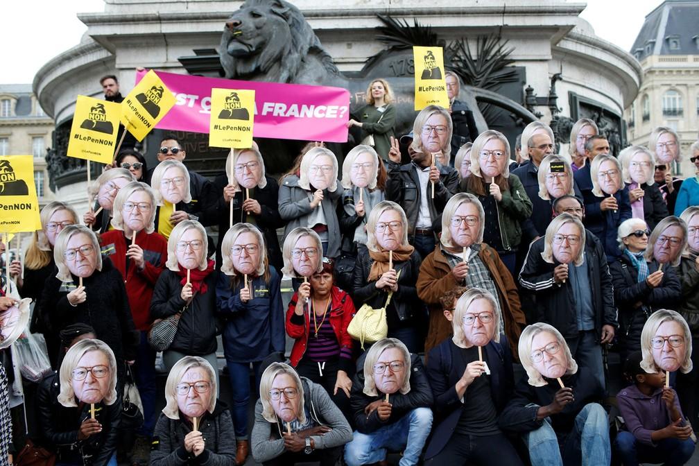 Ativistas usam máscara de Jean-Marie Le Pen, fundador do partido de extrema-direita da França, com o o cabelo da filha dele, Marine Le Pen, candidata à presidente do país, durante marcha do Dia do Trabalhador em Paris nesta segunda-feira, dia 1º de maio de 2017 (Foto: Gonzalo Fuentes/Reuters)